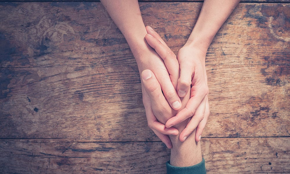 dual diagnosis rehab patient holding loved one's hand
