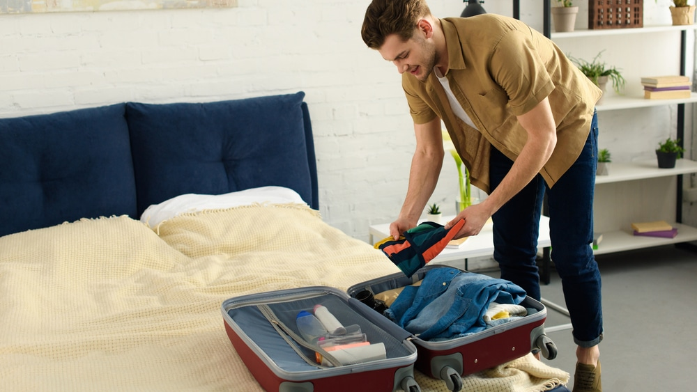 31 tips for rehab North Jersey Recovery - A man puts one more shirt in his suitcase which is laying open on his bed. Tonight he leaves for rehab to over come his substance abuse.