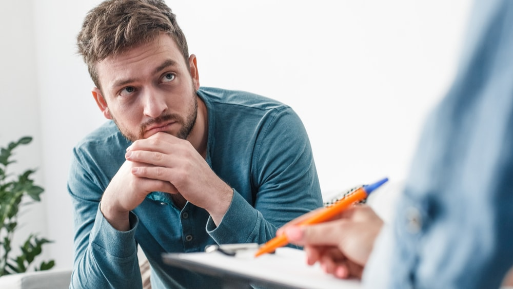 What Causes Addiction North Jersey Recovery Center - A young man sits with a professional and experienced psychiatrist to determine what the cause of his addictions are and the best treatment plan for him based on his addiction needs and requirements