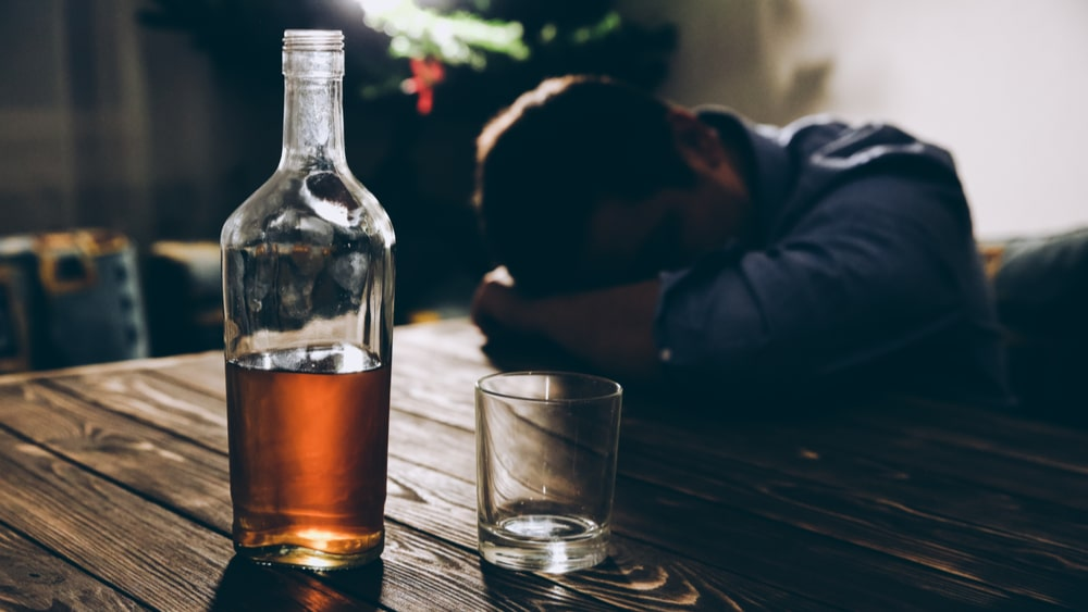 Alcohol Addiction and Abuse: Learn About Alcoholism North Jersey Recovery Center - A middle-aged man is struggling with alcohol abuse and addiction, while sitting alone and drinking liquor at a bar.