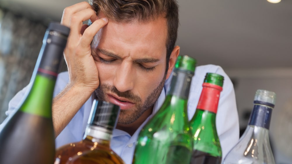 Alcohol Withdrawal and Detox North Jersey Recovery Center - A man is lying in bed where he is experiencing alcohol withdrawal symptoms after binge drinking for a long period of time, and is debating taking Adderall for alcohol withdrawal to ease his symptoms but is unsure if this is a smart idea.