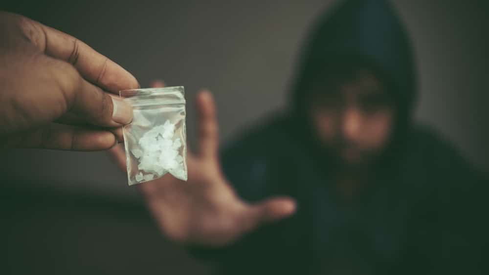 Crack Cocaine Symptoms and Warning Signs North Jersey Recovery Center - A young man buys crack cocaine off the street from a drug dealer to support his addiction.
