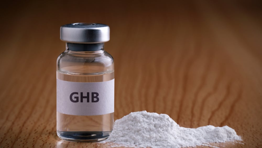 GHB Addiction and Abuse - North Jersey Recovery Center - A vile of GHB sits next to a small pile of white powder.