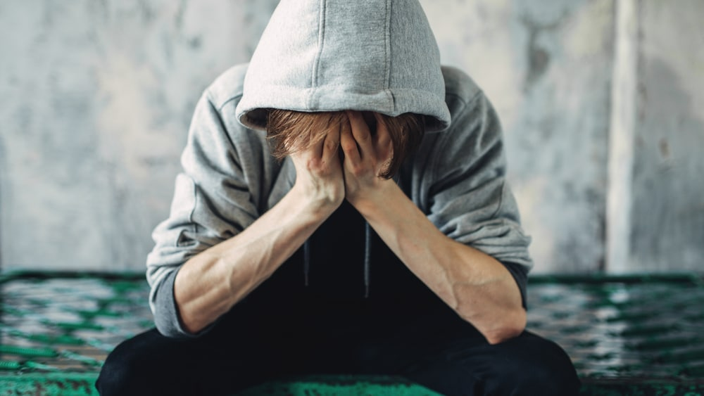 Heroin Withdrawal and Detox North Jersey Recovery Center - A young male is sitting on the street with his head in his hands as he starts to feel the effects of heroin withdrawal symptoms.