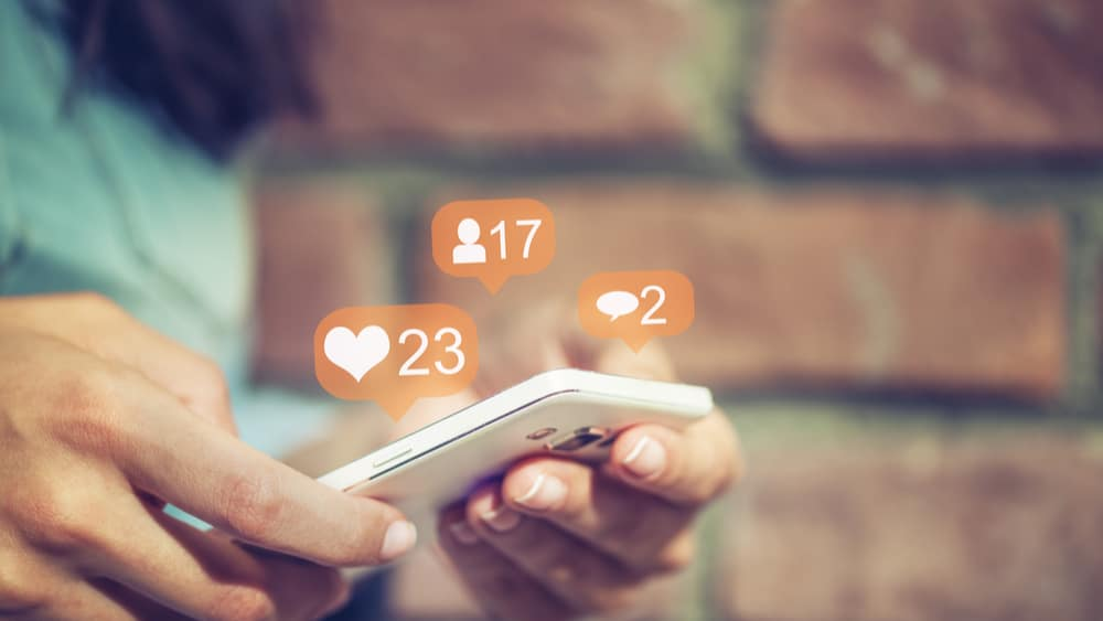 Social Media and Drug Use North Jersey Recovery Center - A woman is centered in on her phone, checking all of her social media accounts, which can lead to negative effects for those struggling with addiction when it comes to how the media influences drug use