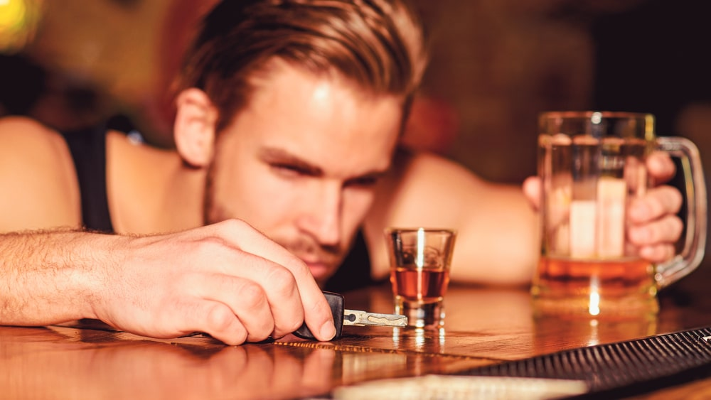 Alcoholism - North Jersey Recovery Center - An alcoholic sits at a bar with his keys in one hand, a beer in the other as his head is on the bar staring at a shot of whiskey.