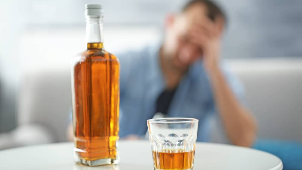 Alcohol and the Liver - North Jersey Recovery Center - A bottle of alcohol and a glass sit on a table. IN the background slightly blurred is a man sitting in the couch worried that his alcoholism has damaged his liver.