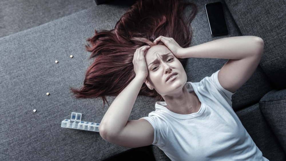 """Librium Addiction, Abuse, and Treatment - Chlordiazepoxide North Jersey Recovery Center - A young woman is laying half on the floor and half on the couch and grabbing her head with her Librium anxiety medication spread out behind her on the couch as she wonders: """"What is Librium?"""" and has she developed an addiction to the medication."""