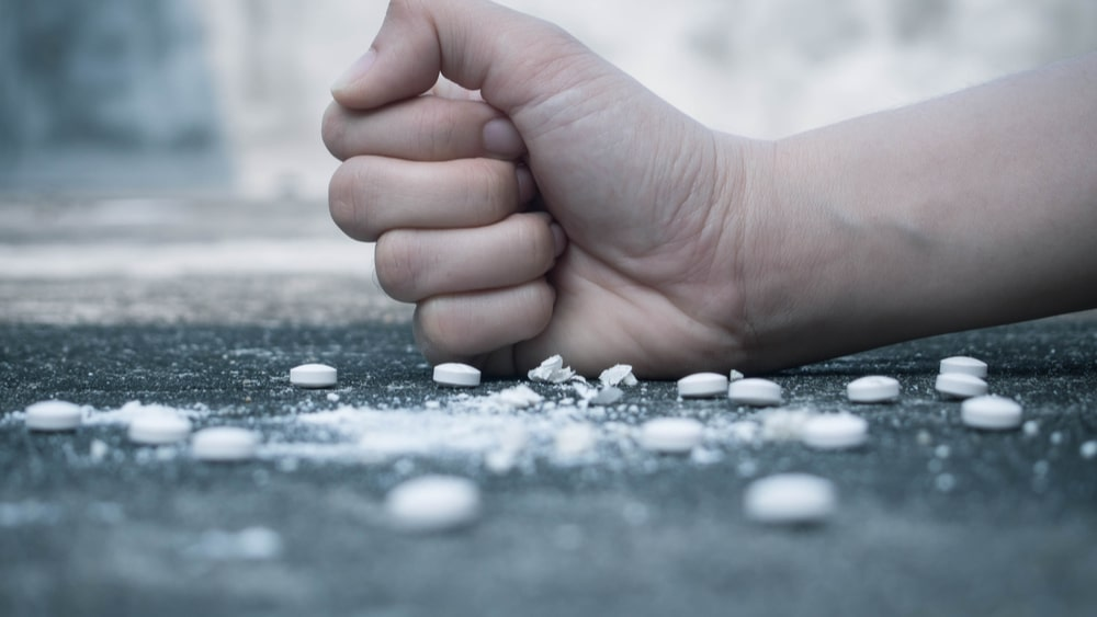 Snorting Xanax or Other Benzodiazepines North Jersey Recovery Center - A man is using his fist to crush up Xanax and other benzodiazepines as he prepares for snorting Xanax to achieve the high the substance provides more quickly than swallowing the pill.