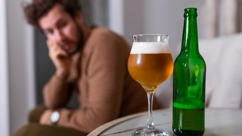 The 7 Types of Alcoholics North Jersey Recovery Center - A depressed young male sits on a couch staring at a beer bottle and a glass filled with beer as he contemplates his alcohol use and if he fits into the different types of alcoholics or not.