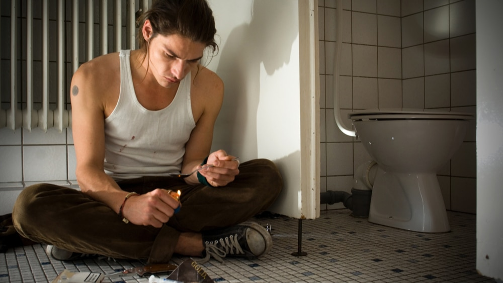 Heroin Symptoms and Warning Signs North Jersey Recovery Center - A young man sits on the floor in a public restroom as he gets ready to inject heroin into his body and, unfortunately, experience heroin symptoms like heroin eyes.